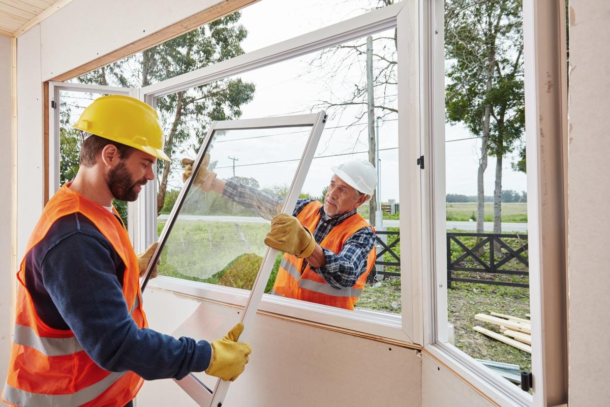 Zwei Monteure bauen ein Fenster ein