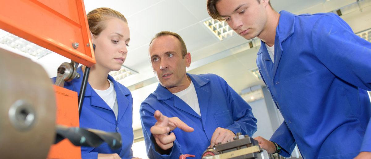 Schülerpraktikanten und Ausbilder in einem Handwerksbetrieb