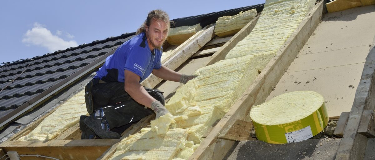 Dachdecker dämmt ein Dach