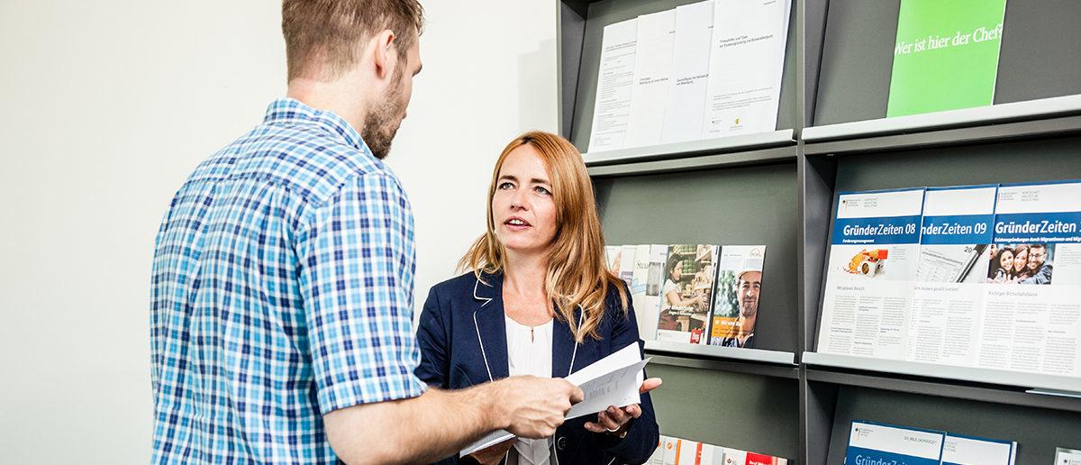 Mann und Frau unterhalten, Mann hält Broschüre