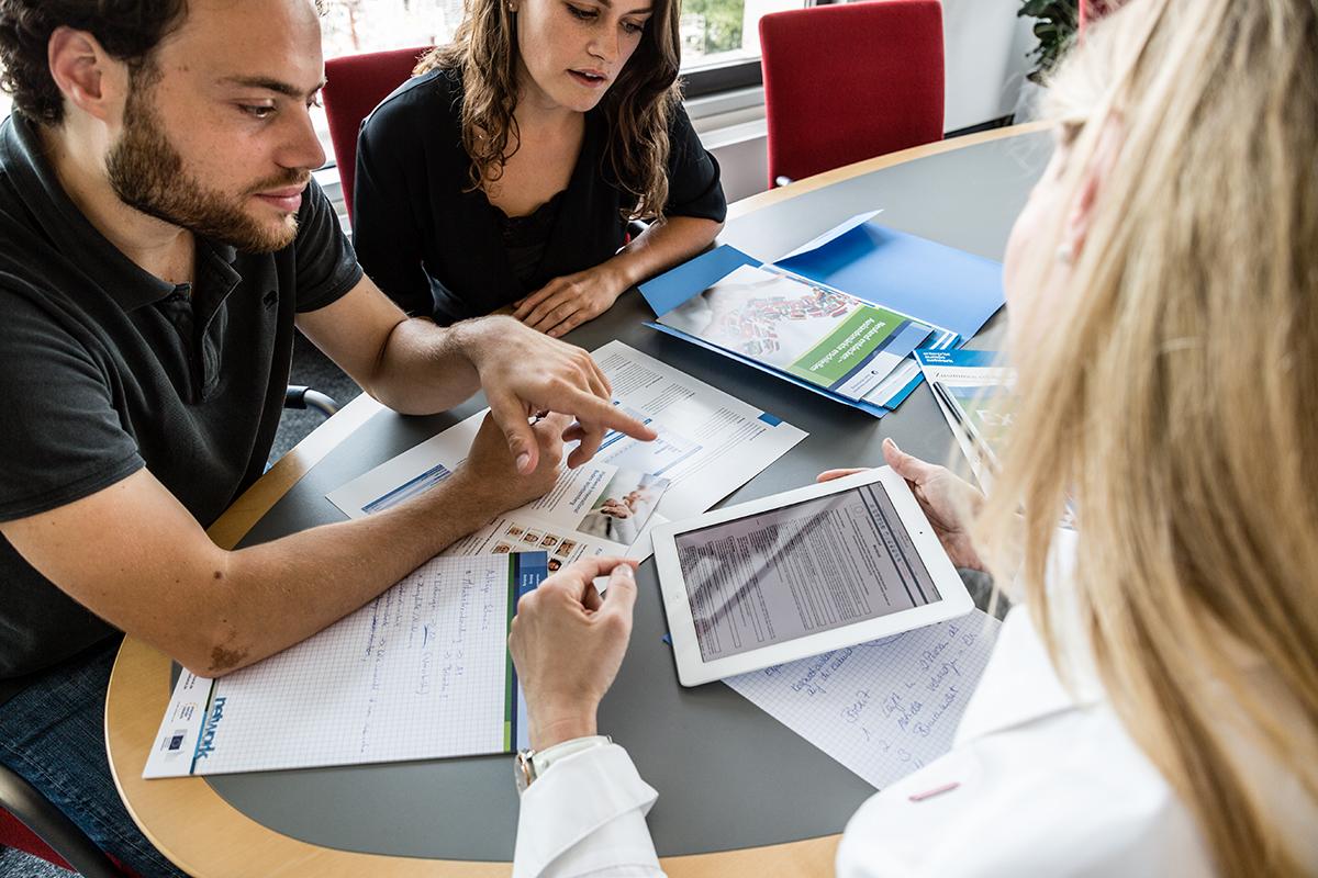 Eine Mann und eine Frau informieren sich bei einer Beraterin.