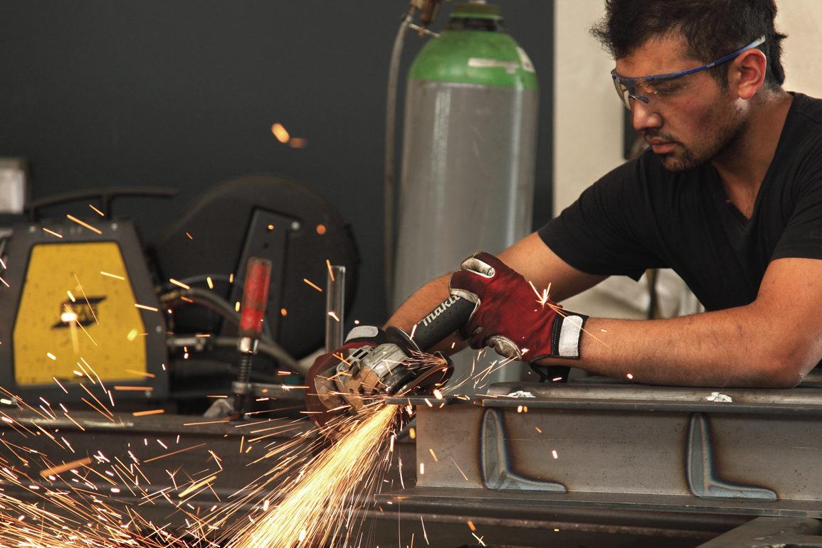 Metallbauer bearbeit ein Metallstück sodass Funken fliegen