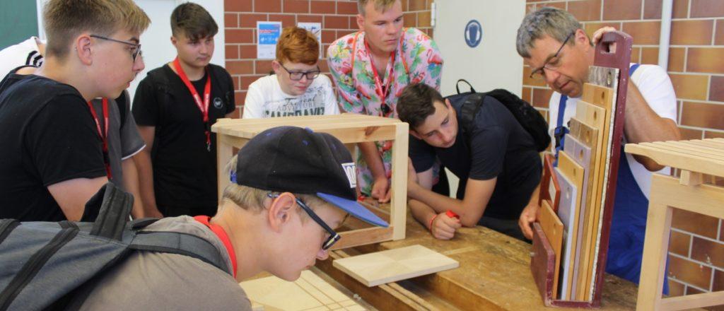 Tischler-Ausbilder zeigt den Schülern verschiedene Holzarten
