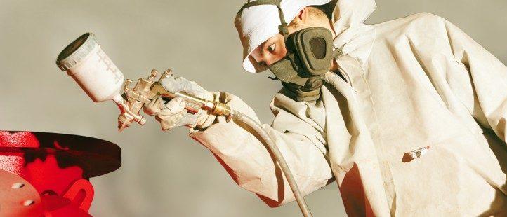 Ein Maler- und Lackiere besprüht ein Metallobjekt mit Lackierfarbe
