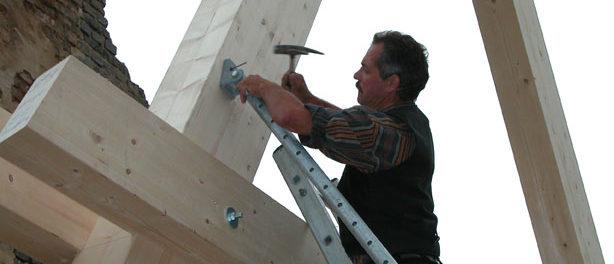 Zimmerer hämmert einen Holzbalken