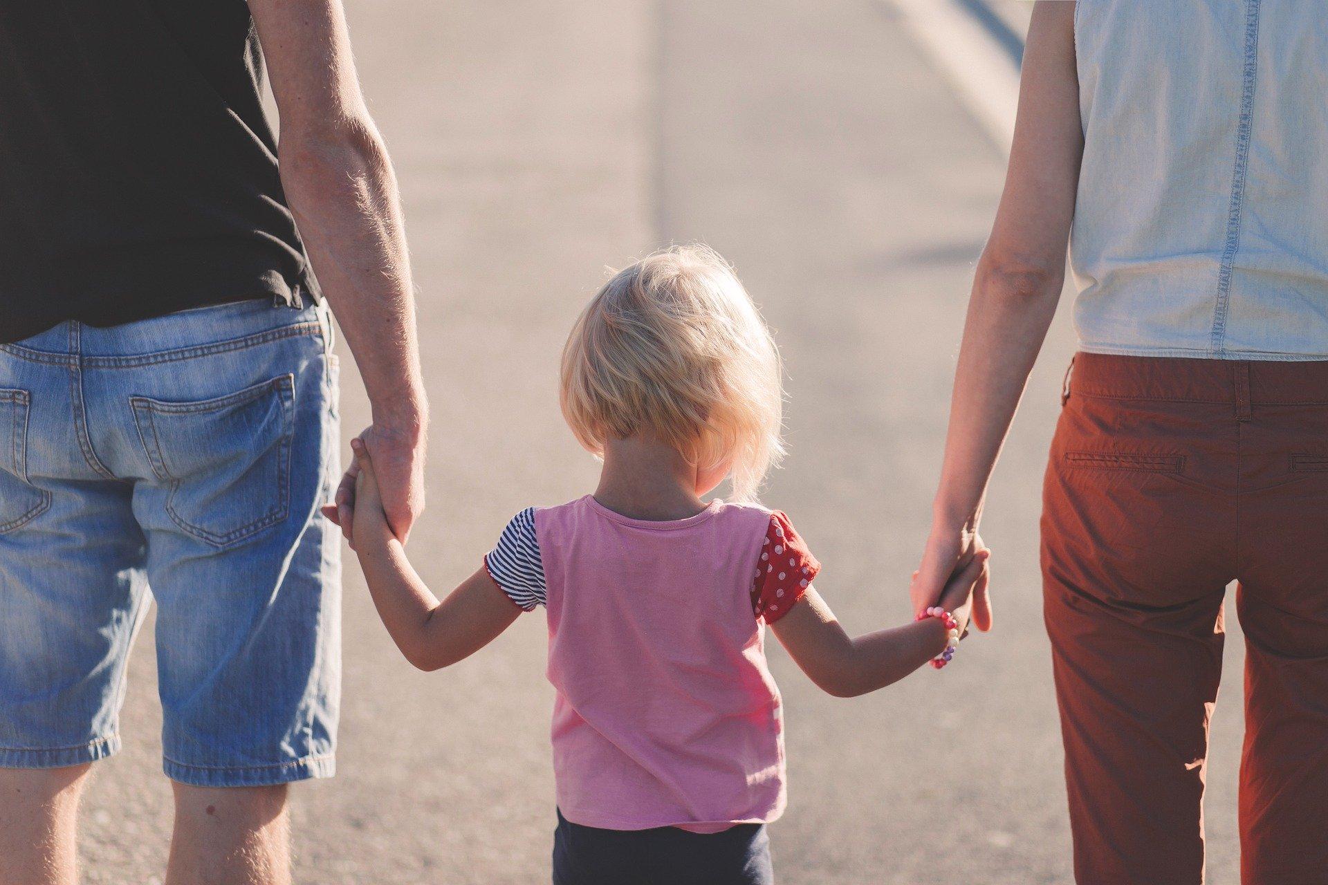 Vater, Kind, Mutter fassen sich an der Hand