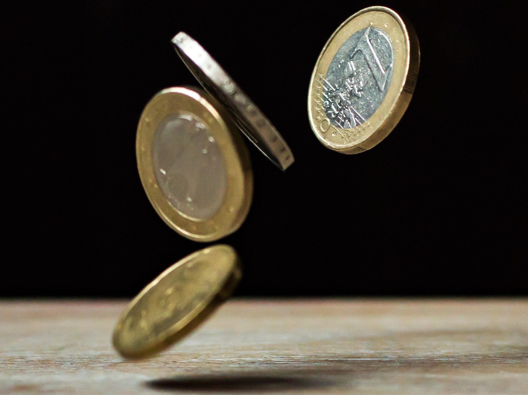 1-Euro-Münzen fallen auf einen Holztisch