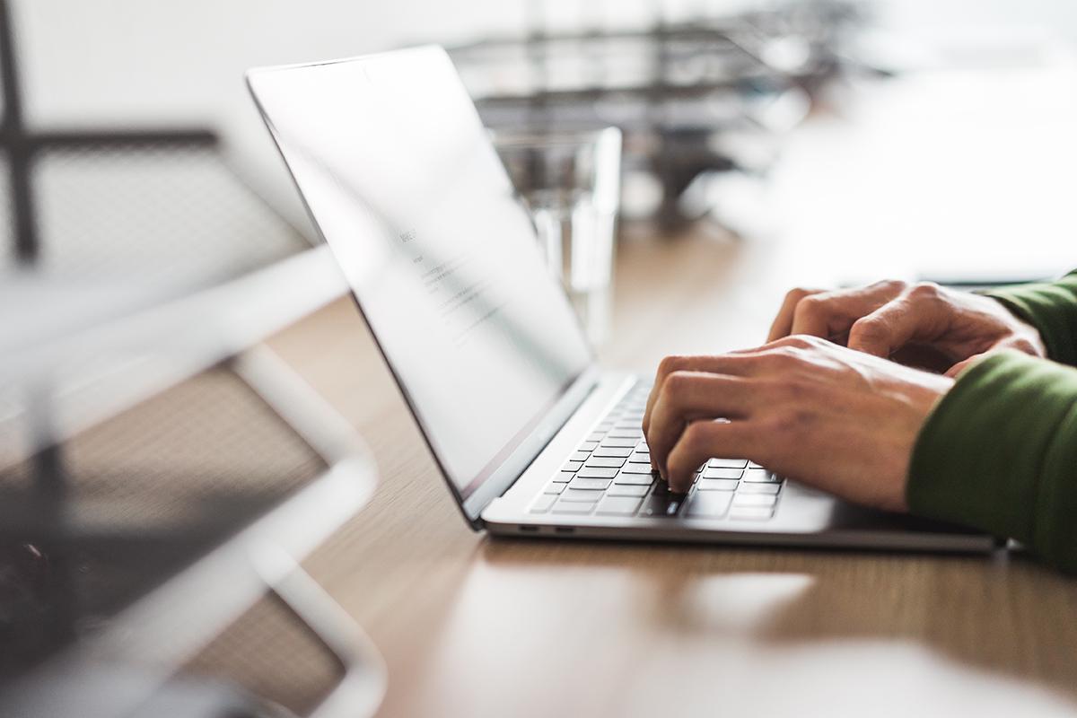 Mann schreibt auf einem Laptop