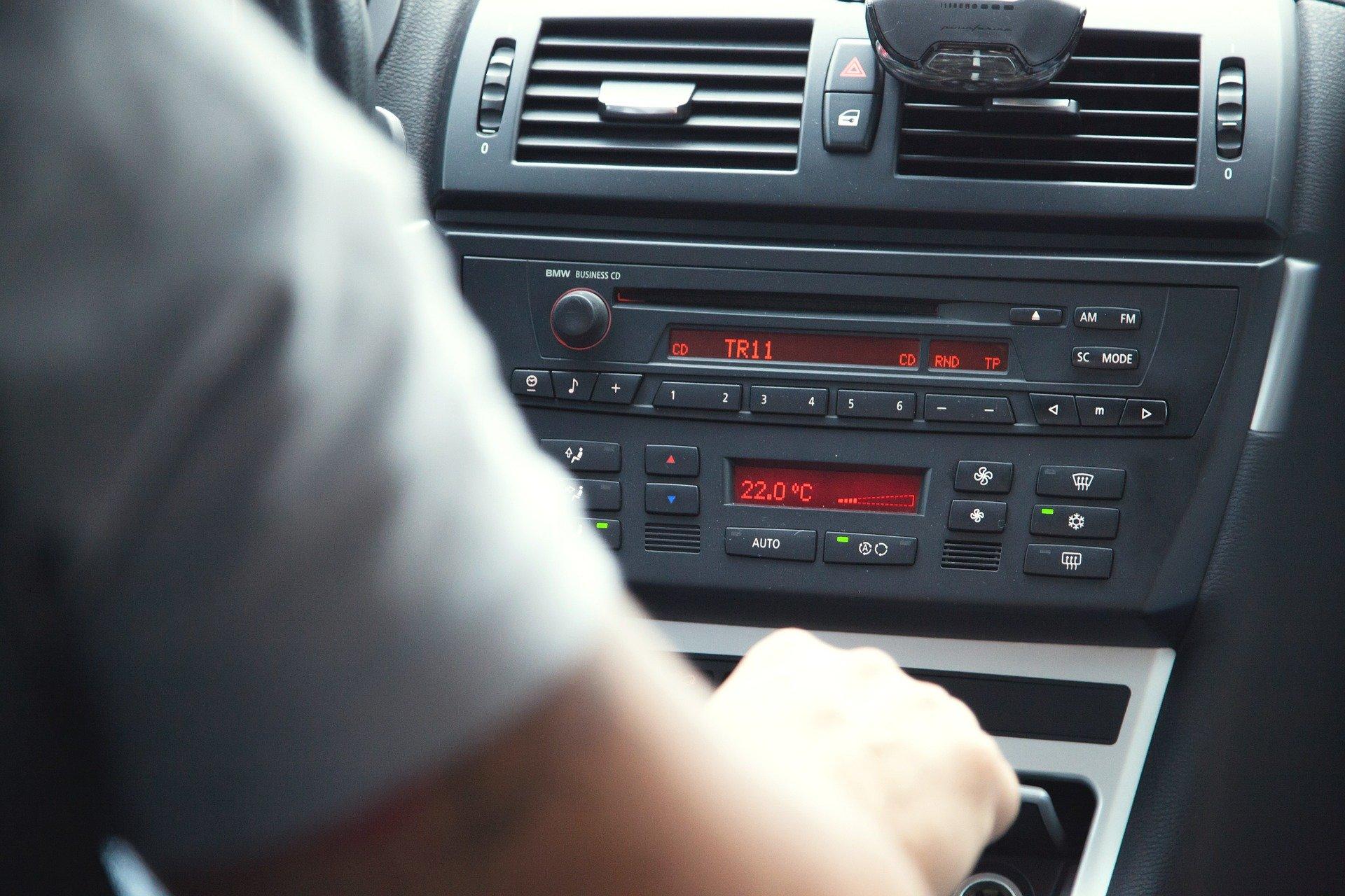 Fahrer sitzt im Auto und hört Radio