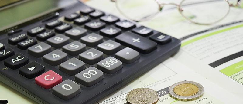 Ein Taschenrechner liegt auf dem Schreibtisch. Daneben Akten und Geldmünzen