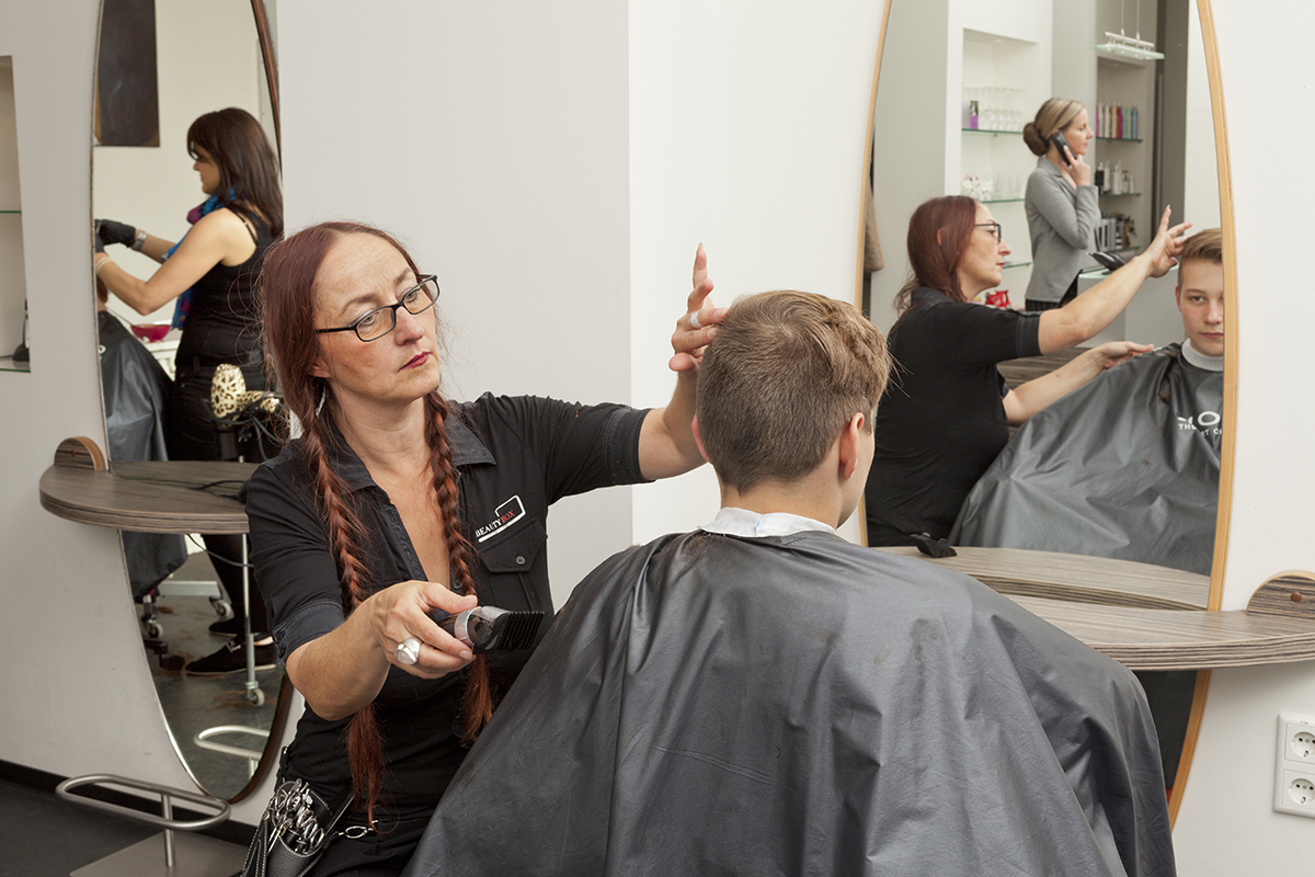 Friseur kämmt Mann die Haare und hat in der anderen Hand eine Schere