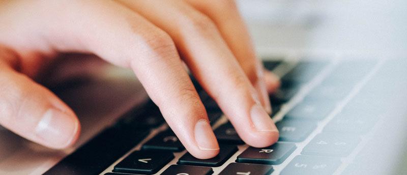 Hand liegt auf einer Computertastatur