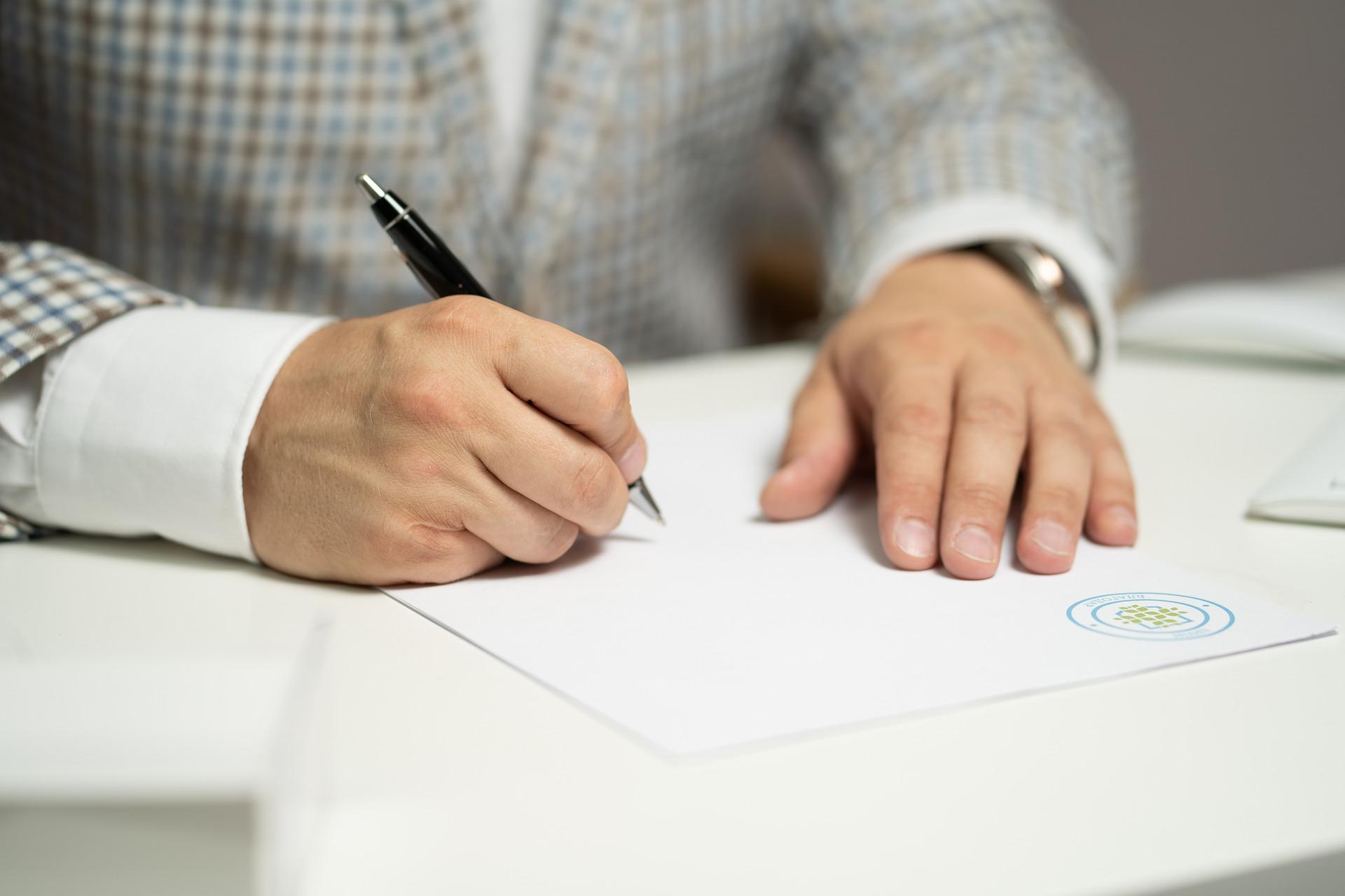 Mann unterschreibt ein Dokument