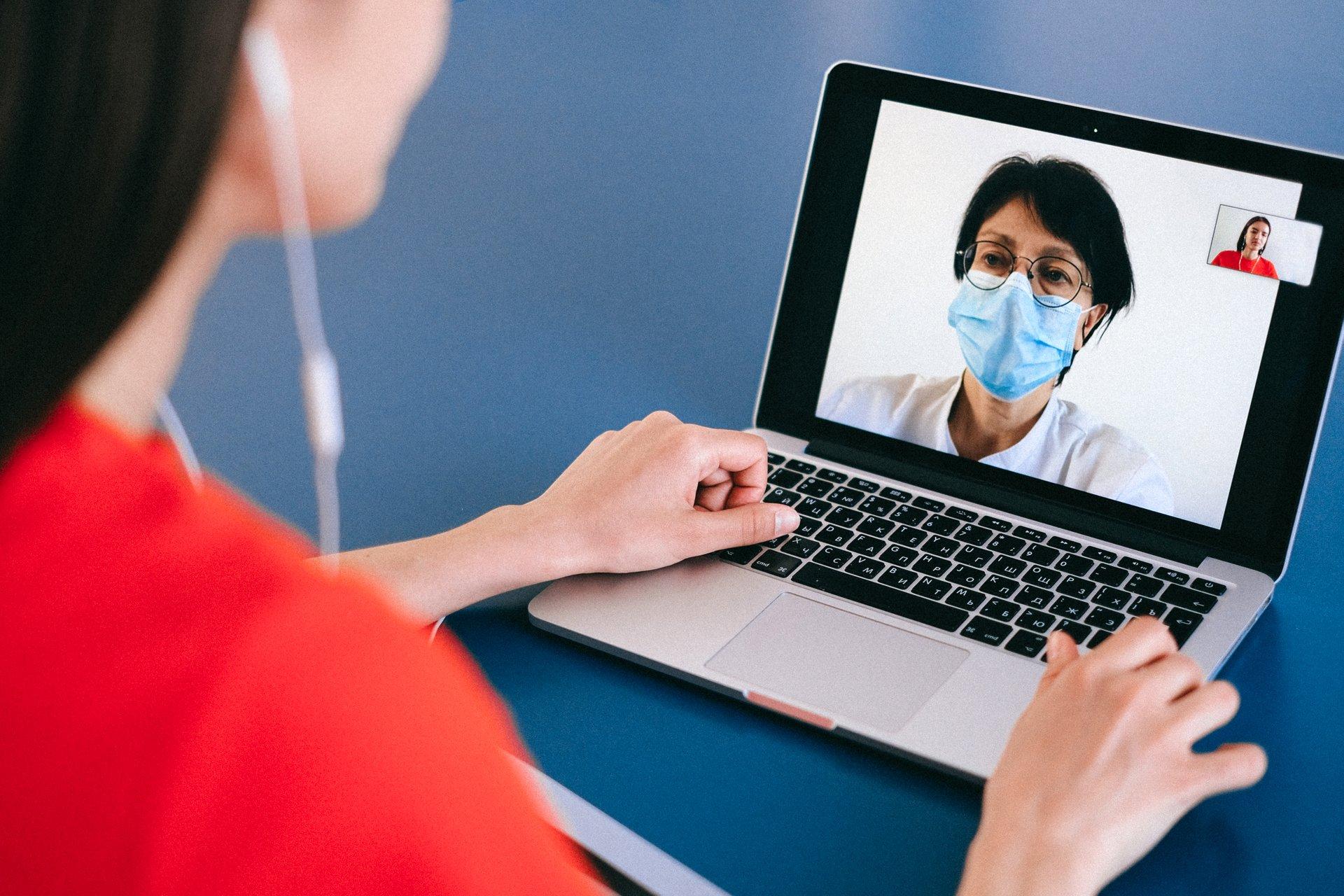 Frau bei eine Videosprechstunde am Laptop mit Arzt