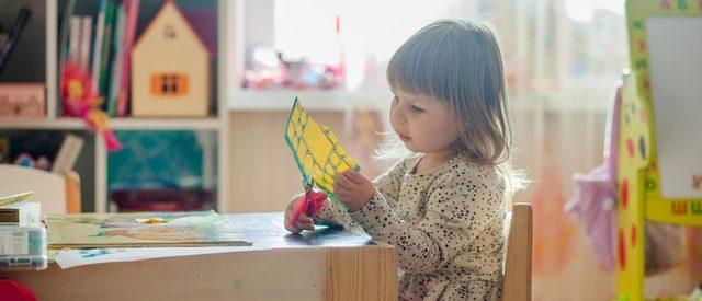 Mädchen sitzt am Tisch und schneidet ein Blatt im Kindergarten