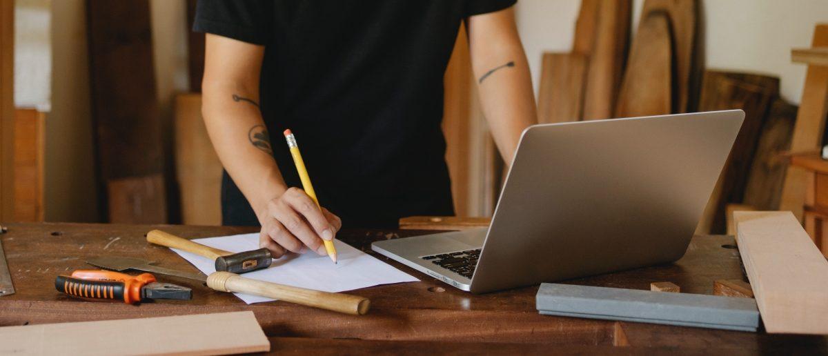 Janger Handwerker arbeitet mit tradionionellen Tischlerwerkzeugen und Laptop an seinem Werktisch