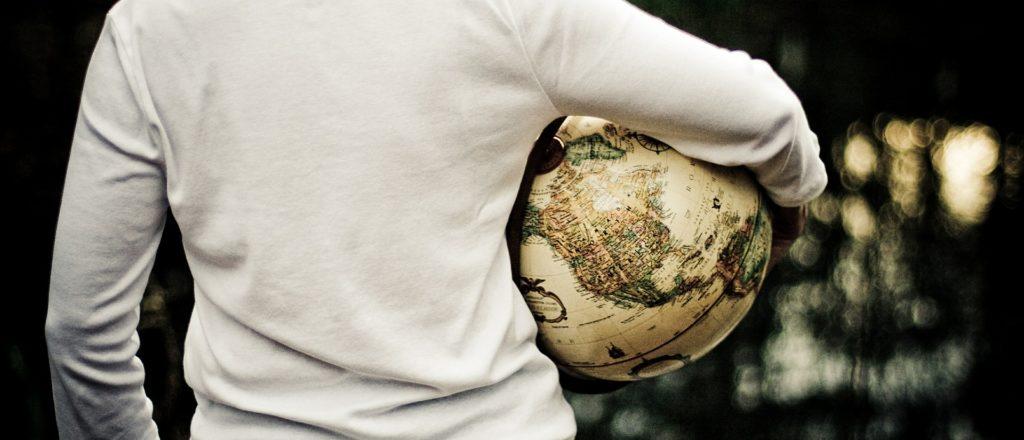 Junger Mensch von hinten hält einen Globus unter seinem Arm
